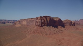 AX135_119 - 6K stock footage aerial video orbit Spearhead Mesa in a desert valley, Monument Valley, Utah, Arizona