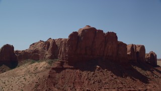 AX135_132 - 6K stock footage aerial video of approaching a rugged desert butte, Monument Valley, Utah, Arizona