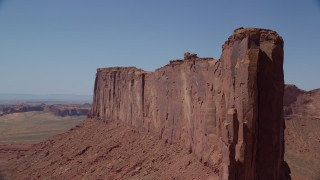 AX135_140 - 6K stock footage aerial video of flying by the steep sides of Meridian Butte, Monument Valley, Utah, Arizona