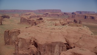 AX135_173 - 6K stock footage aerial video of flying by a rugged desert mesa in a hazy valley, Monument Valley, Utah, Arizona