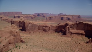 AX135_175 - 6K stock footage aerial video of flying by a group of desert buttes and mesas, Monument Valley, Utah, Arizona