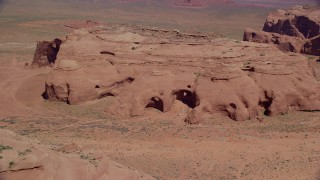 AX135_179 - 6K stock footage aerial video of flying by caves, rock formations in Monument Valley, Utah, Arizona