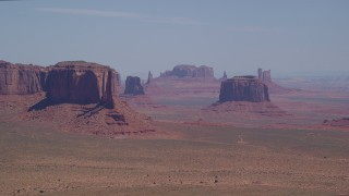 AX135_182 - 6K stock footage aerial video of flying by rugged buttes in hazy desert valley, Monument Valley, Utah, Arizona