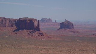 AX135_183 - 6K stock footage aerial video of passing by rugged mesas and buttes in a hazy desert valley, Monument Valley, Utah, Arizona