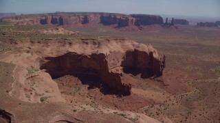 AX135_187 - 6K stock footage aerial video of a view of Mitchell Mesa in hazy desert valley, Monument Valley, Utah, Arizona