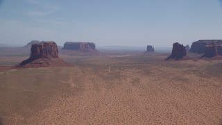 AX135_193 - 6K stock footage aerial video of passing by open desert with buttes and mesas, Monument Valley, Arizona, Utah