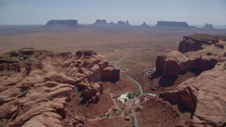 AX135_201 - 6K stock footage aerial video of passing Goulding between Oljeto Mesa and Rock Door Mesa, Navajo Nation Reservation, Utah, Arizona
