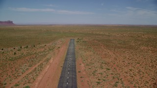 AX136_001 - 6K stock footage aerial video of flying over a runway toward wide desert valley, Monument Valley Airport, Utah