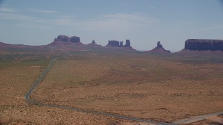 AX136_002 - 6K stock footage aerial video of flying by Highway 163 leading to buttes in Monument Valley Arizona, Utah
