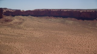 AX136_010 - 6K stock footage aerial video of flying over desert valley, approaching Mitchell Mesa, Monument Valley, Utah, Arizona