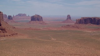 AX136_018 - 6K stock footage aerial video pass by towering buttes and mesas in a desert valley, Monument Valley, Utah, Arizona