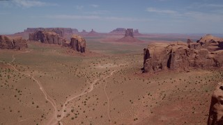 AX136_024 - 6K stock footage aerial video of passing desert buttes and mesas to approach more landmarks in Monument Valley, Utah, Arizona