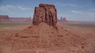 AX136_030 - 6K stock footage aerial video tilt from desert valley to reveal East Mitten Butte, Monument Valley, Utah, Arizona