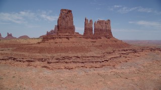 AX136_036 - 6K stock footage aerial video tilt from desert valley to reveal towering buttes, Monument Valley, Utah, Arizona