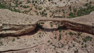 AX136_122 - 6K stock footage aerial video approach Owachomo Bridge, tilt and orbit the arch, Natural Bridges National Monument, Utah