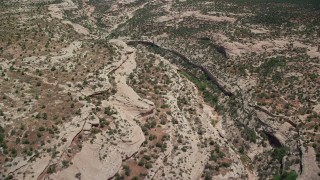 AX136_124 - 6K stock footage aerial video of flying over desert canyon, Natural Bridges National Monument, Utah