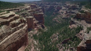 AX136_142 - 6K stock footage aerial video of flying by and descending into Arch Canyon, Utah