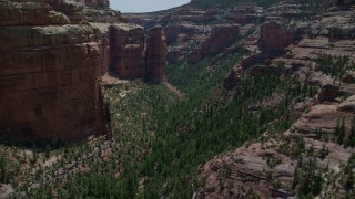 AX136_144 - 6K stock footage aerial video of approaching rock formation while flying through Arch Canyon, Utah