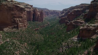 AX136_146 - 6K stock footage aerial video of flying around a rock formation and through Arch Canyon, Utah