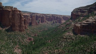 AX136_149 - 6K stock footage aerial video of flying over trees, passing rock formations in Arch Canyon, Utah