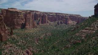 AX136_150 - 6K stock footage aerial video of trees and tall rock formations in Arch Canyon, Utah