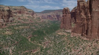 AX136_154 - 6K stock footage aerial video of near tall rock formations in Arch Canyon, Utah