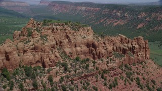 AX136_187 - 6K stock footage aerial video of flying over butte, reveal dirt roads in canyon, Manti-La Sal National Forest, Utah
