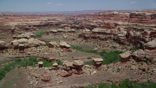 AX136_212 - 6K stock footage aerial video of flying over boulders, rock formations and canyons, Canyonlands National Park, Utah