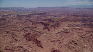 AX136_247 - 6K stock footage aerial video pan across and approach canyons, buttes near White Rim cliffs, Canyonlands National Park, Utah