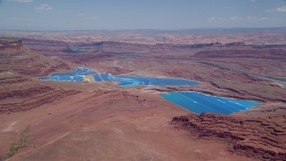 AX136_268 - 6K stock footage aerial video of approaching potash ponds and desert valley, Moab, Utah