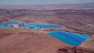 AX136_269 - 6K stock footage aerial video of flying toward potash ponds in a desert valley, Moab, Utah