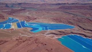 AX136_270 - 6K stock footage aerial video of potash ponds in a desert valley, Moab, Utah