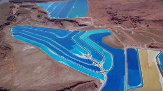 AX136_274 - 6K stock footage aerial video of flying away from potash ponds in an arid desert valley, Moab, Utah