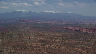 AX137_006 - 6K stock footage aerial video of desert rock formations, distant snow-capped mountains, Arches National Park, Utah