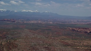 AX137_008 - 6K stock footage aerial video of a wide view of rock formations, snow-capped mountains, Arches National Park, Utah