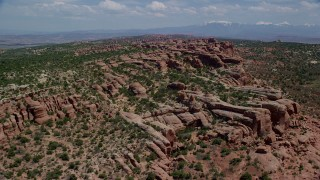 AX137_037 - 6K stock footage aerial video fly over rock formations and green desert vegetation in Eagle Park, Arches National Park, Utah