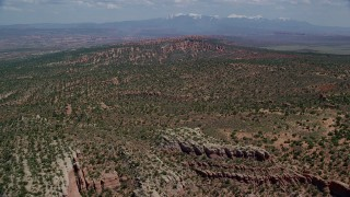 AX137_043 - 6K stock footage aerial video fly over cliffs and desert plants toward Devil's Garden, Arches National Park, Utah