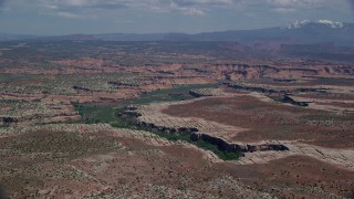 AX137_054 - 6K stock footage aerial video of flying over open desert toward Salt Wash Canyons, Arches National Park, Utah