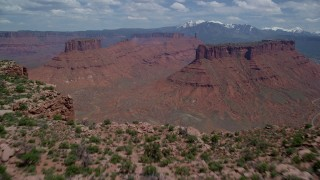 AX137_089 - 6K stock footage aerial video fly low over Dry Mesa to reveal buttes and Parriott Mesa, Colorado River, Moab, Utah