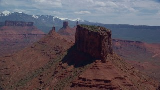 AX137_094 - 6K stock footage aerial video of flying by a butte with Castleton Tower in the background, Moab, Utah