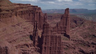 AX137_107 - 6K stock footage aerial video flyby Ancient Art to approach The Titan and other rock formations at Fisher Towers, Utah