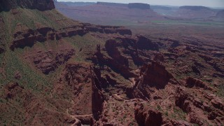 AX137_122 - 6K stock footage aerial video of approaching canyon with dirt path in Fisher Towers, Utah