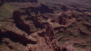AX137_123 - 6K stock footage aerial video of flying over dirt path through canyon in Fisher Towers, Utah