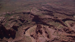 AX137_124 - 6K stock footage aerial video of a dirt road through canyon in Fisher Towers, Utah