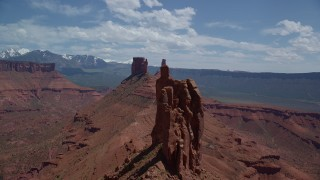 AX137_133 - 6K stock footage aerial video of flying over a butte to approach two other buttes in Moab, Utah
