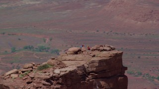 AX137_139 - 6K stock footage aerial video orbit two rock climbers on top of Castleton Tower in Moab, Utah