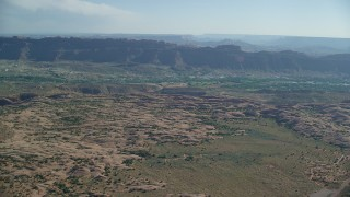 AX138_036 - 6K stock footage aerial video fly over rock formations to approach small desert town,  Sand Flats Recreation Area, Moab, Utah