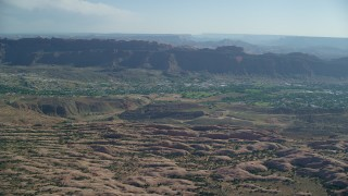 AX138_037 - 6K stock footage aerial video approach small desert town from rock formations, Sand Flats Recreation Area, Moab, Utah