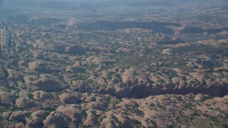 AX138_038 - 6K stock footage aerial video of domed desert rock formations and sparse vegetation, Sand Flats Recreation Area, Utah