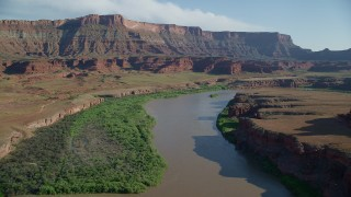 AX138_065 - 6K stock footage aerial video follow Colorado River toward a mesa, Moab, Utah